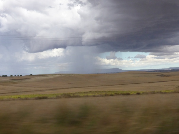 """After being on the Camino for 25 days, this is the closest we got to rain!!  During the summer time, it is interesting that almost 50% of the rainfall is from thunderstorms on this prairie region. Picture taken from our cab window as we retraced our steps back to Burgos for the train  to Madrid. What had taken us 3 days to walk we made by car in less than 90 minutes. As we watched the familiar places whiz by, we realized how fortunate we were to have experienced this journey """"at the speed of life""""."""