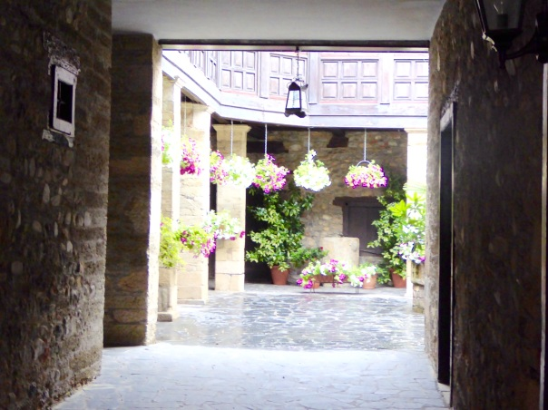 So many of the streets in Europe seem to be faced with buildings that come right to the sidewalk. In fact behind the car and front entrance doors are  entrance eays to beautiful courtyards. Here we are looking into a gardened area that is like a courtyard back garden.