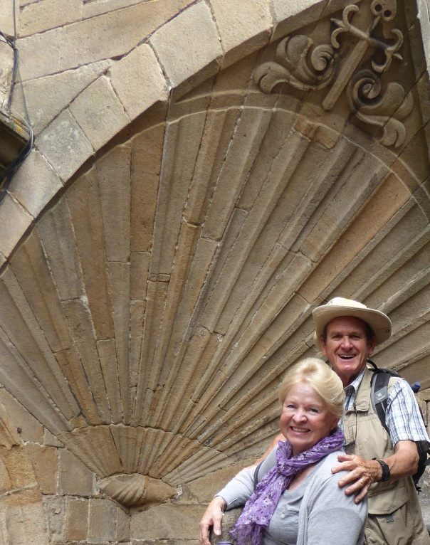 A more subdued couple standing before the giant she'll symbolizing the end of the Camino.